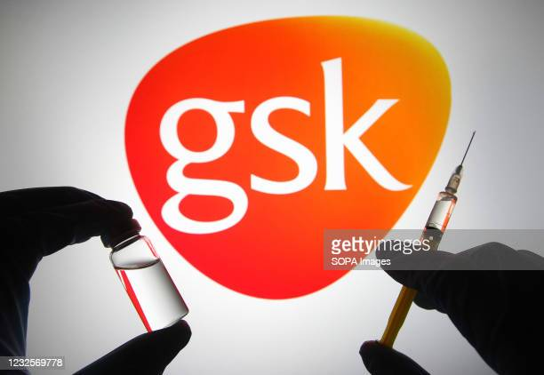 In this photo illustration, silhouette of hands in medical gloves hold a medical syringe and a vial in front of GSK logo of a pharmaceutical industry...