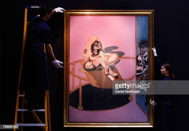 In this photo illustration Sotheby's employee's appear to hold a painting by Francis Bacon called Study of Nude with figure in a mirror during a...