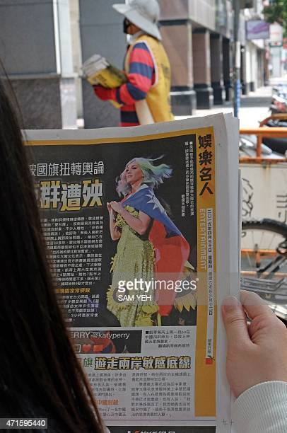 In this photo illustration taken on April 30 a local resident reads a newspaper showing US singer Katy Perry wearing Taiwan's national flag in Taipei...