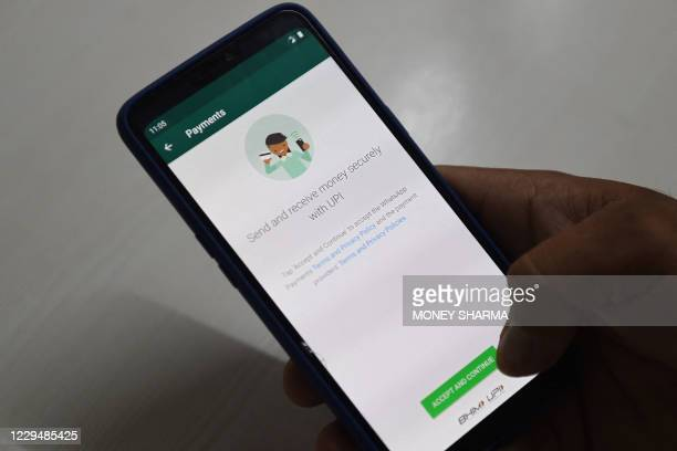 In this photo illustration taken on November 6 a user checks the Facebook's WhatsApp application payment feature on his mobile phone in Faridabad. -...