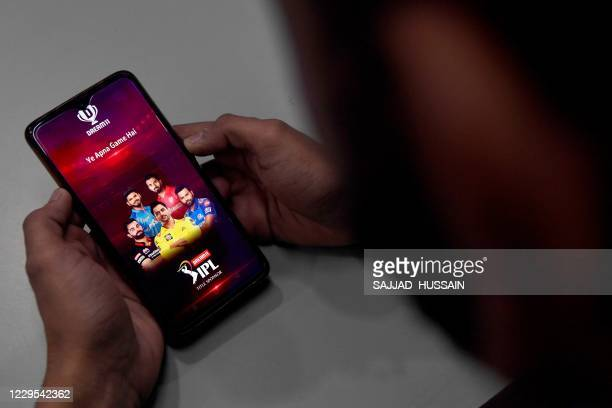 In this photo illustration taken on October 12 a user checks the Dream11 application of the Indian Premier League cricket tournament, on his mobile...