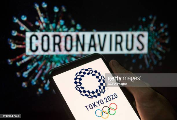 In this photo illustration the 2020 Tokyo Olympics logo seen displayed on a smartphone with a computer model of the COVID-19 coronavirus on the...