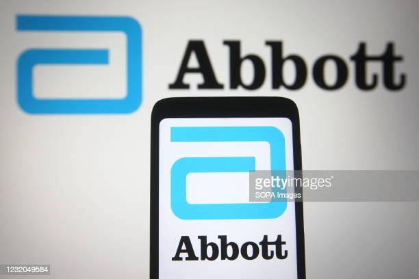In this photo illustration, the Abbott Laboratories logo of the US medical device company seen displayed on a smartphone and a pc screen.