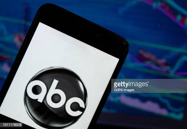 The ABC News logo seen displayed on a smart phone with a background of a stock market shedle ABC News is the news division of the American...