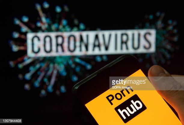 In this photo illustration the adult pornographic video sharing website Pornhub logo seen displayed on a smartphone with a computer model of the...