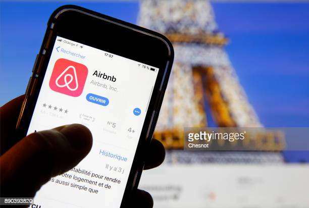 In this photo illustration the Airbnb app is displayed in front of a computer screen showing an announcement on the Airbnb website on December 11...