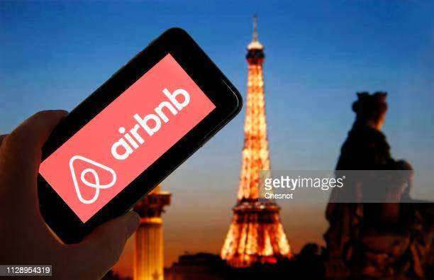 In this photo illustration the Airbnb logo is displayed on the screen of an iPhone in front of a computer screen displaying a picture of the Eiffel...