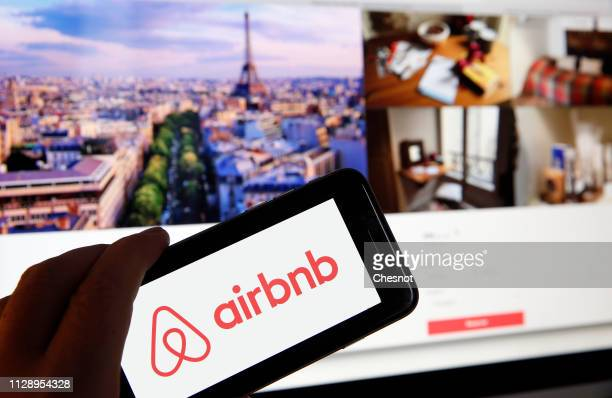 In this photo illustration the Airbnb logo is displayed on the screen of an iPhone in front of a computer screen displaying announcements of rental...
