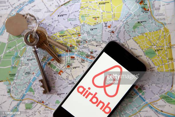 In this photo illustration the Airbnb logo is displayed on the screen of an iPhone placed on a map of the city of Paris on February 11 2019 in Paris...