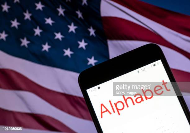 In this photo illustration the Alphabet logo seen displayed on a smartphone with a background of an American Flag According to the New York Stock...