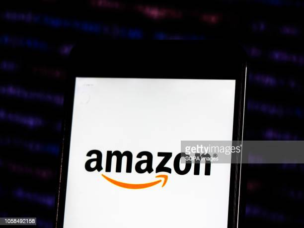 In this photo illustration the Amazon logo seen displayed on a smartphone Amazoncom Inc doing business as Amazon is an American electronic commerce...