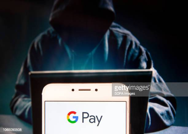 American online payment platform owned by Google Google Pay logo is seen on an Android mobile device with a figure of hacker in the background