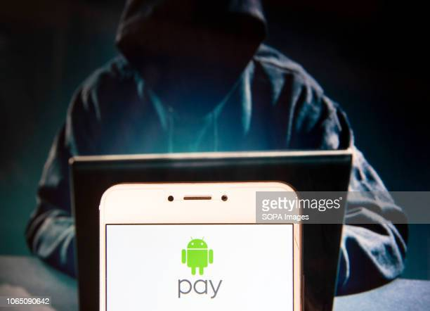 American online payment platform owned by Google Android Pay logo is seen on an Android mobile device with a figure of hacker in the background