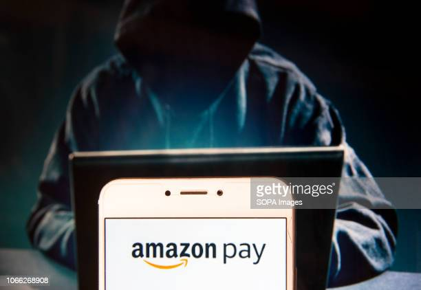American online payment platform owned by Amazon Amazon Pay logo is seen on an Android mobile device with a figure of hacker in the background