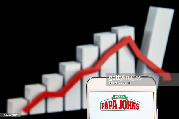 In this photo illustration the American pizza restaurant franchise Papa John's Pizza logo is seen displayed on an Android mobile device with a loss...
