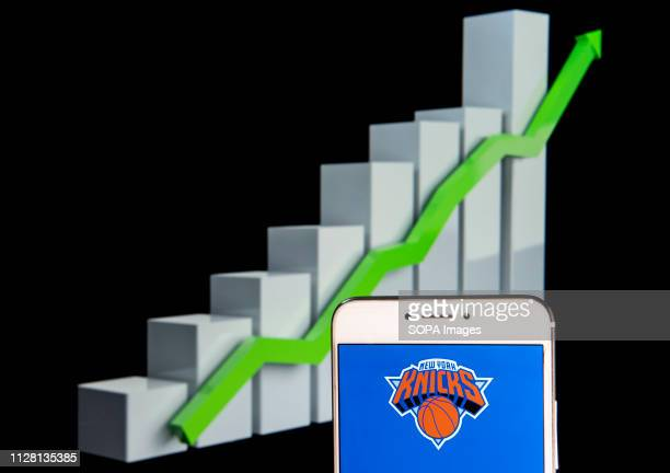 In this photo illustration the American professional basketball team the New York Knicks logo is seen displayed on an Android mobile device with an...