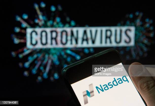 In this photo illustration the American stock exchange index Nasdaq logo seen displayed on a smartphone with a computer model of the COVID-19...