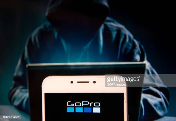 American technology company and manufacturer known for its action cameras GoPro logo is seen on an Android mobile device with a figure of hacker in...