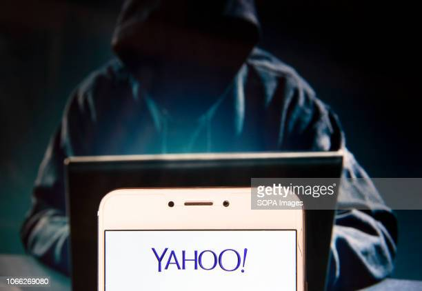 In this photo illustration, the American web services provider company Yahoo! logo is seen displayed on an Android mobile device with a figure of...