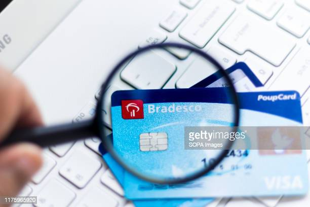 In this photo illustration the Banco Bradesco logo is seen displayed through a magnifying glass on the credit card