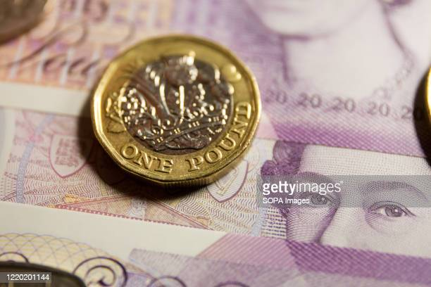In this photo illustration The Bank of England twenty pounds note with the image of Queen Elizabeth II and The British one pound coin are seen...