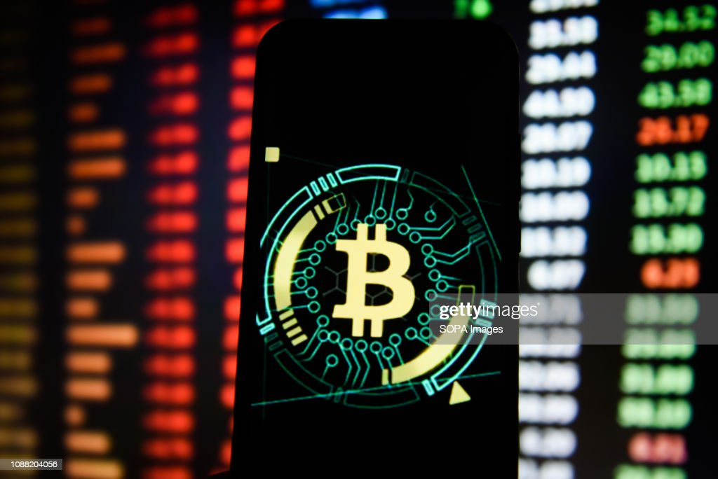 Bitcoin logo is seen on an android mobile phone : News Photo