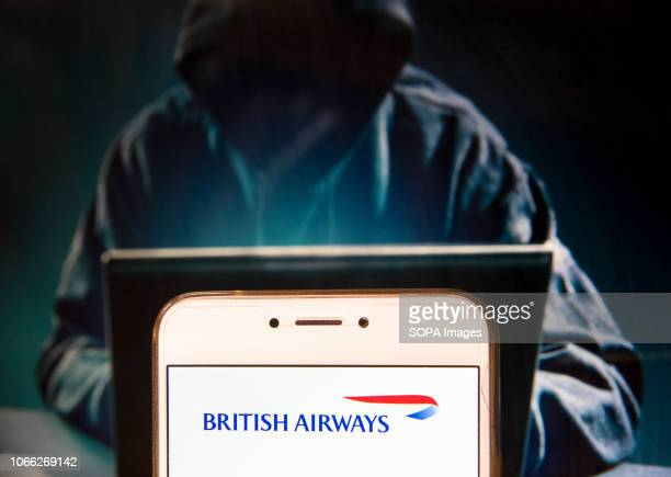 In this photo illustration the British Airways logo is seen displayed on an Android mobile device with a figure of a hacker in the background