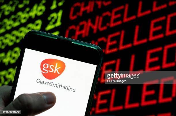 In this photo illustration the British multinational pharmaceutical company GlaxoSmithKline logo is seen on an Android mobile device with a computer...
