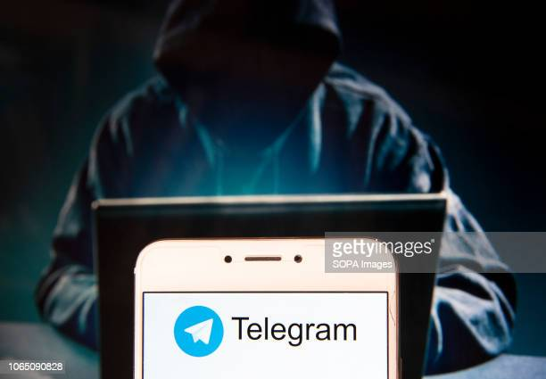 In this photo illustration, the Cloud based instant messaging Telegram logo is seen displayed on an Android mobile device with a figure of hacker in...