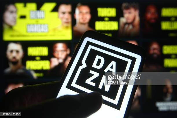 In this photo illustration the DAZN logo of a sports video streaming service is seen on a smartphone with its website in the background.