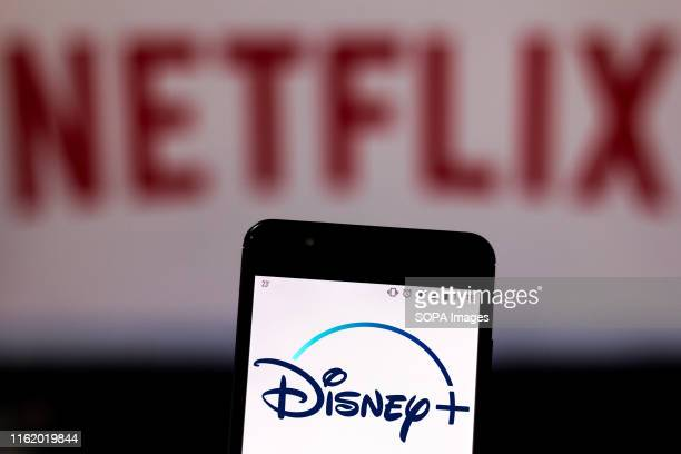 In this photo illustration the Disney Plus logo is seen displayed on a smartphone and logo Netflix on the blurred background.