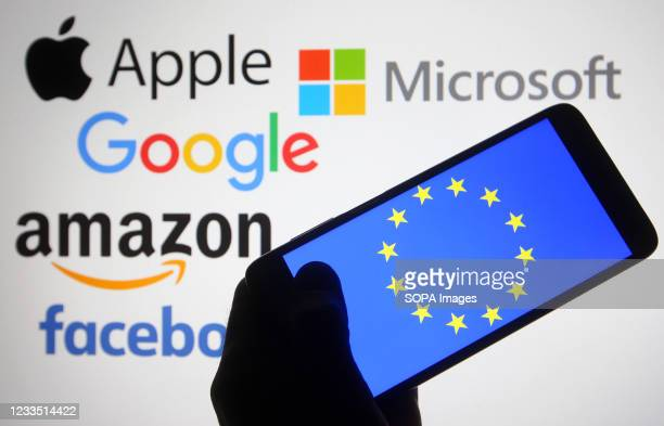 In this photo illustration, the EU flag is seen on a smartphone screen in front of Apple, Microsoft, Google, Amazon and Facebook logos.