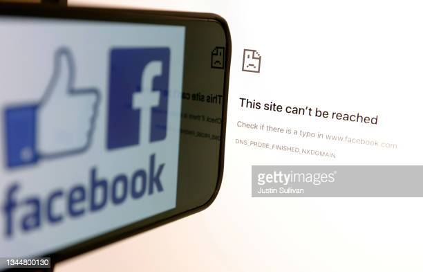 In this photo illustration, the Facebook logo is displayed next to a screen showing that Facbook service is down on October 04, 2021 in San Anselmo,...
