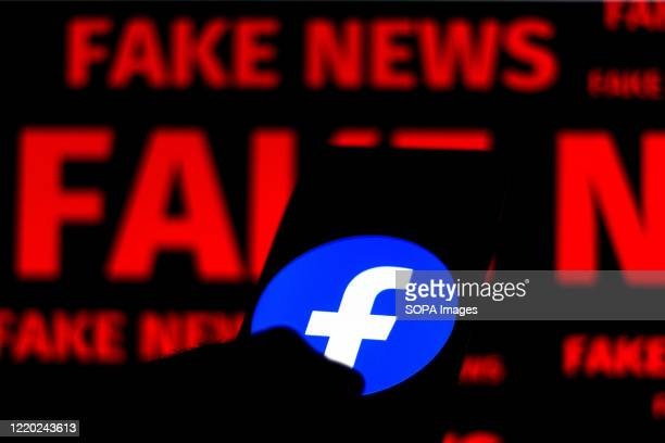 "In this photo illustration the Facebook logo is displayed on a smartphone and a red alerting word ""FAKE NEWS"" on the blurred background."