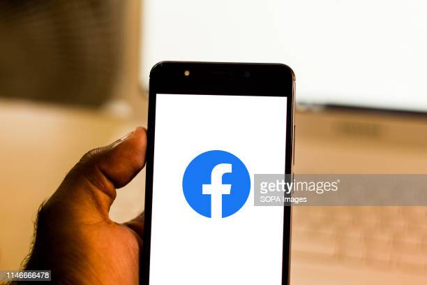 In this photo illustration the Facebook logo is seen displayed on a smartphone