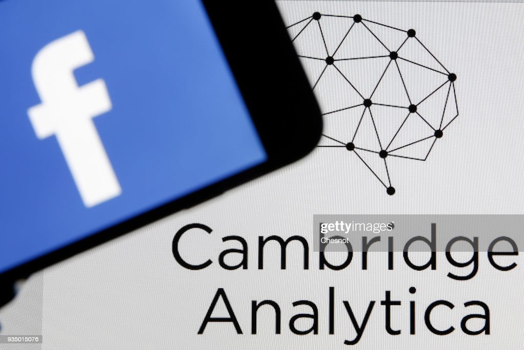 In this photo illustration the Facebook logo is seen on the screen of an iPhone in front of a computer screen showing a Cambrige Analytica logo on March 20, 2018 in Paris, France. Cambridge Analytica is accused of collecting the personal information of 50 million users of the Facebook social network without their consent and would have used it to develop software to predict and influence voter voting during the campaign American election according to the New York Times and the Guardian. Facebook share price fell by more than 5% Monday shortly after the opening of Wall Street.
