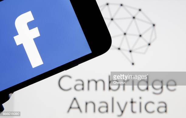 In this photo illustration the Facebook logo is seen on the screen of an iPhone in front of a computer screen showing a Cambrige Analytica logo on...