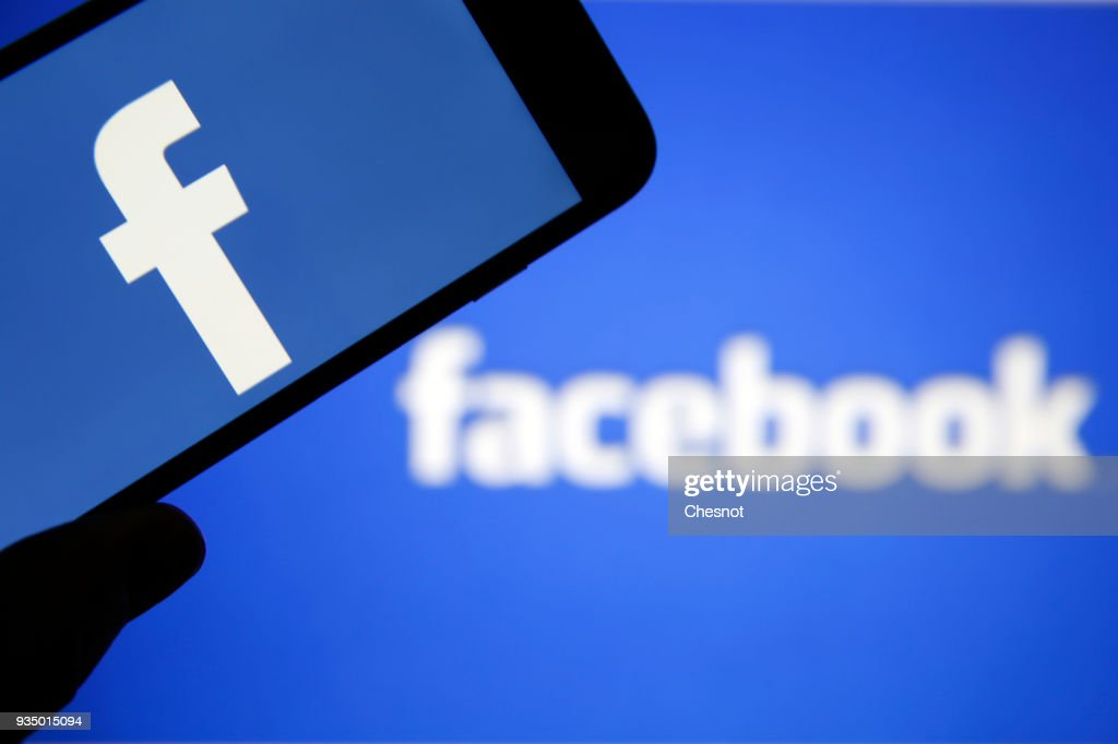 In this photo illustration the Facebook logo is seen on the screen of an iPhone in front of a computer screen showing a Facebook logo on March 20, 2018 in Paris, France. Cambridge Analytica is accused of collecting the personal information of 50 million users of the Facebook social network without their consent and would have used it to develop software to predict and influence voter voting during the campaign American election according to the New York Times and the Guardian. Facebook share price fell by more than 5% Monday shortly after the opening of Wall Street.