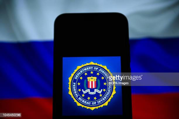 In this photo illustration, the FBI logo is seen displayed on an Android mobie phone with Russia's flag in the background.