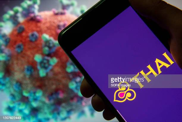 In this photo illustration the flag carrier airline of Thailand Thai Airways logo seen displayed on a smartphone with a computer model of the COVID19...