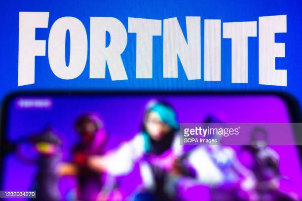 In this photo illustration the Fortnite logo is seen on a smartphone and a pc screen.