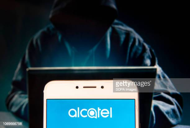 French global telecommunications equipment company Alcatel logo is seen on an Android mobile device with a figure of hacker in the background