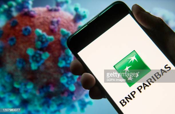 In this photo illustration the French international banking group BNP Paribas logo seen displayed on a smartphone with a computer model of the...
