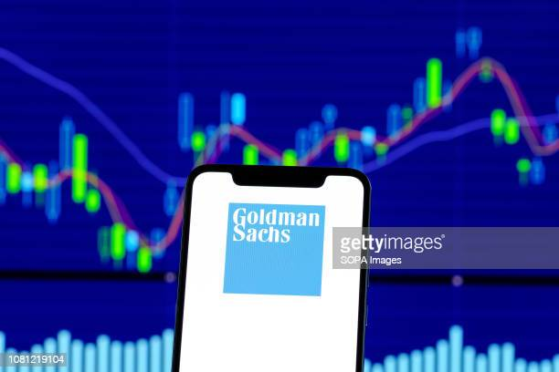 In this photo illustration the Goldman Sachs logo is seen displayed on an Android smartphone over stock chart
