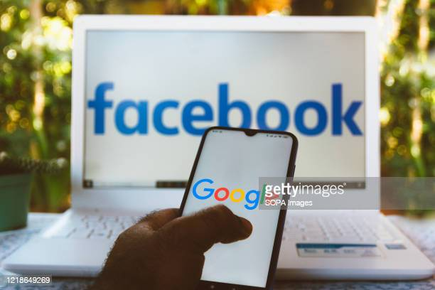 In this photo illustration the Google logo is displayed on a smartphone with a Facebook logo on the computer screen in the background.