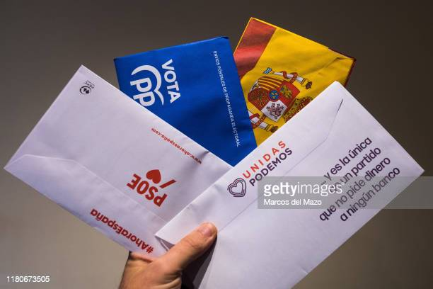 In this photo illustration, the hand of a man showing postal mail of some of the main Spanish political parties that contains the ballots to vote in...