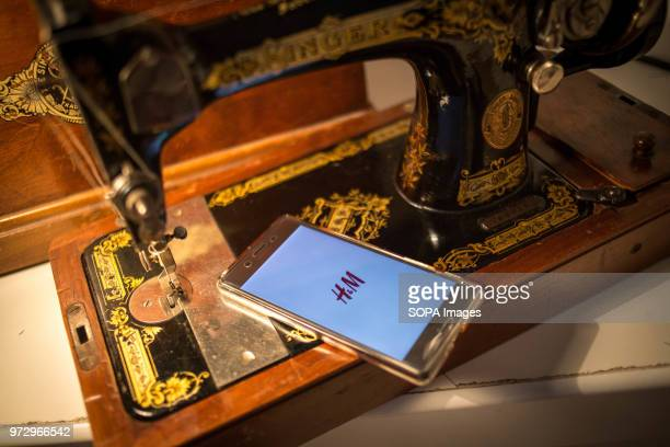 The HM application seen display on a Android Sony smartphone next to a vintage sewing machine 'Singer'