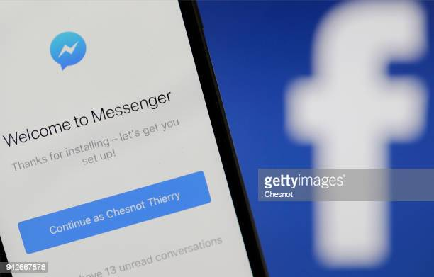 In this photo illustration the home page of the instant messenger 'Messenger' is seen on the screen of an iPhone in front of a computer screen...