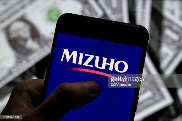 In this photo illustration the Japanese multinational banking and financial services corporation Mizuho Bank logo seen displayed on a smartphone with...
