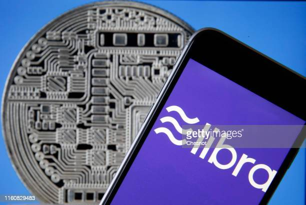 In this photo illustration the Libra logo is displayed on the screen of a mobile phone in front of a computer screen displaying a visual...